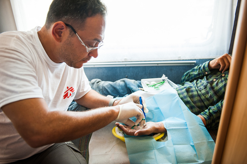 MSF doctor Dimitris Giannousis is treating the burned hand of  Mushtaba at the mobile camper van of MSF at Mytiline port, Lesvos, Greece. <br /> Mushtaba from Afghanistan burned his hand in a forest fire in Turkey few days before coming to Lesvos.
