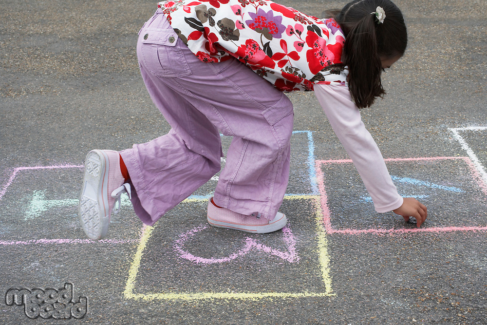 Girl (7-9) playing hop-scotch in school playground