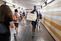 """© Licensed to London News Pictures . 13/07/2018. London, UK. A man carrying a """" Trump is a blood clart """" placard through Charring Cross Underground Station following a march to Trafalgar Square in protest against US President Donald Trump's UK visit . Photo credit: Joel Goodman/LNP"""