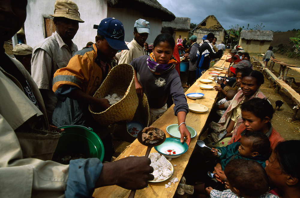 Guests attending a reburial ceremony in Belaveno, Bezanozano Ethnic Area, Madagascar, are served food by the host family. The famadihana, the Madagascan reburial ceremony, is a custom in the highlands of Madagascar. The purpose of the ritual is to induce the ancestors to impart their blessings to their descendants, as without those blessings one cannot have a good life. The famadihana is held during the cooler half of the year, when the dead are said to be freezing in their graves and therefore need new clothing.