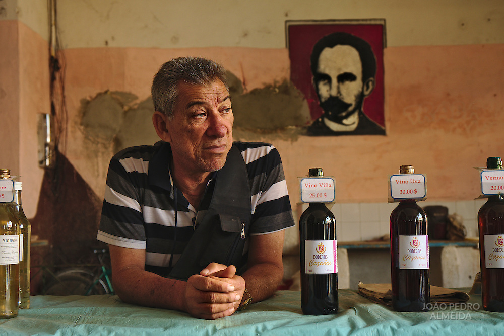 Wine seller at Cienfuegos market with an image of Jose Marti, on the heroes of Cuba independence, in the background