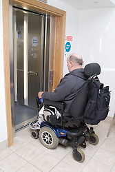 Male wheelchair user entering a lift at his local sports leisure centre,