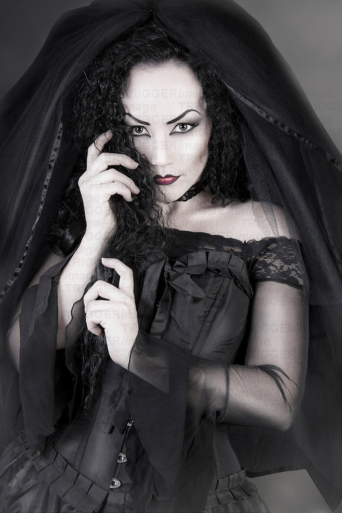 Gothic Bride Widow mourning in black dress looking at camera