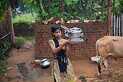 Walking past one of her family's ox after washing some dishes, Tabasum Khatun, 14, is carrying them across the courtyard into her home in Algunda village, pop. 1000, Giridih District, rural Jharkhand, India.