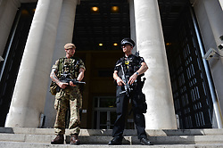 """A soldier joins a police officer outside the Ministry of Defence, London, as armed troops have been deployed to guard """"key locations"""" under Operation Temperer, which is being enacted after security experts warned the Government that another terrorist attack could be imminent."""