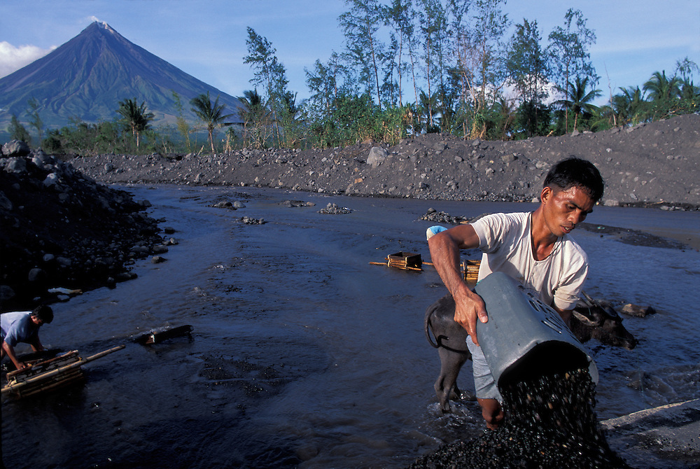 Philippines, Luzon Island, (MR) Robert Vargas sifts through river gravel for pumice near Mayon Volcano