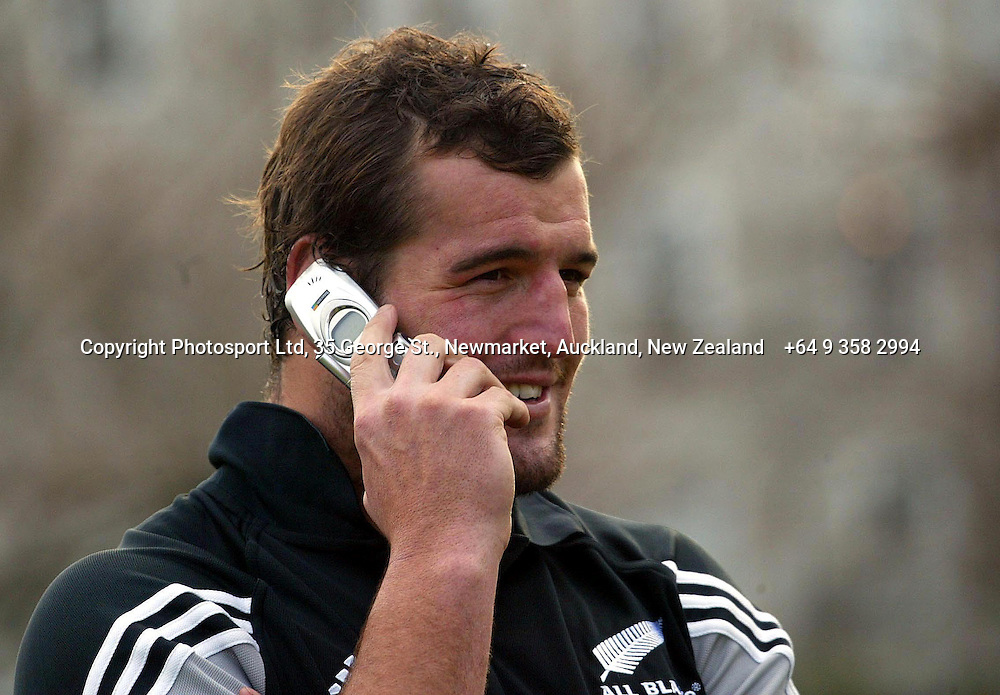 Recalled All Black Carl Hayman smiles as he talks on a cell phone during an All Black Training, 07 June 2004 in Dunedin, prior to the Test match against England on Saturday.<br />