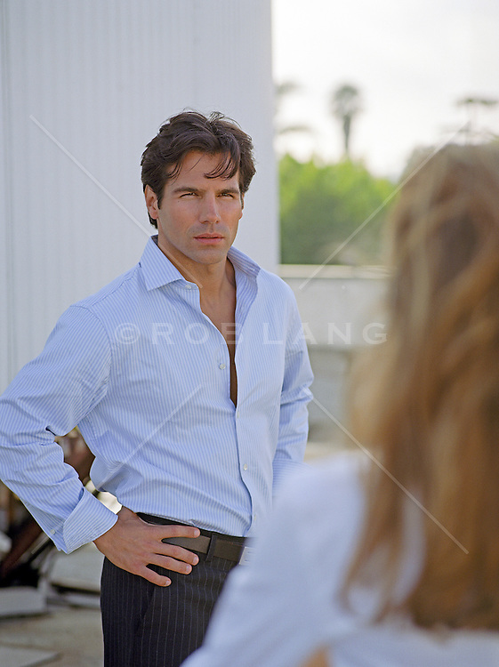 well dressed man standing with hands on his hips looking at a woman outdoors