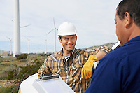 Engineers near wind turbines at wind farm
