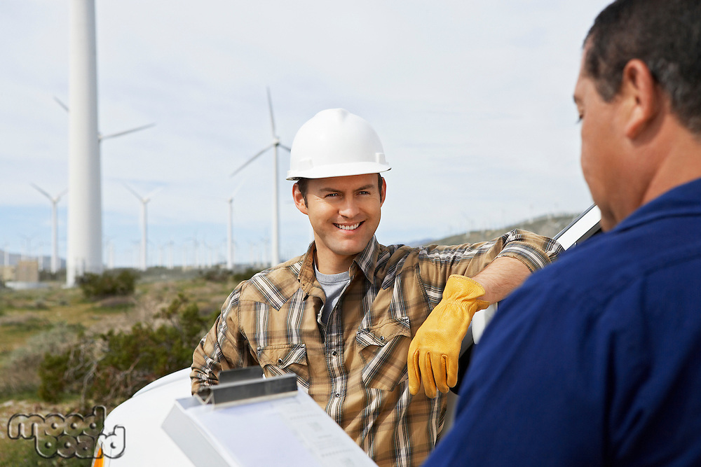 Engineers near wind turbines at wind farm
