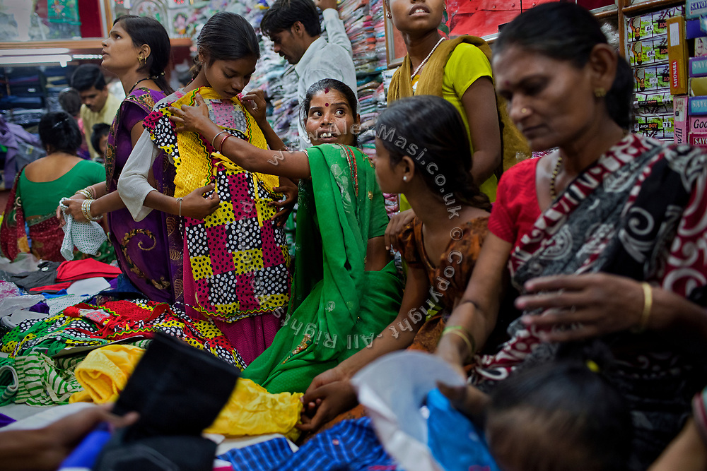 Sangita, 40, (centre) is checking the size of a new dress for her daughter Jyoti, 12, (left) while Poonam, 11, (right) is waiting for her turn, inside a small clothes shop in Bhopal, central India, near the abandoned Union Carbide (now DOW Chemical) industrial complex, site of the infamous '1984 Gas Disaster'.
