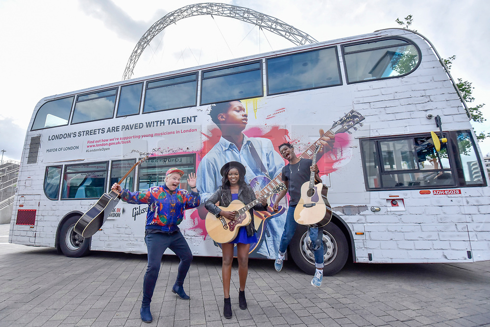 © Licensed to London News Pictures. 21/07/2017. London, UK. Musicians Kal Lavelle, Jay Johnson and Modupe Obasola who have all taken part in the Mayor of London's annual busking competition, stand in front of iconic London buses outside Wembley Stadium to celebrate launch of Gigs, in association with Gibson, on the eve of International Busking Day.  Photo credit : Stephen Chung/LNP