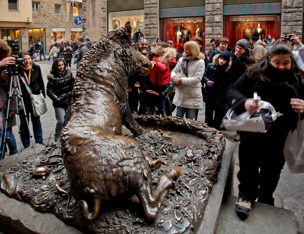 "Bronze statue of the boar (""Il Porcellino"") in the Mercato Nuovo, seen from behind it as a smiling group of people gather round and a boy in a red jacket rubs its nose for luck.  One man has camera on a tripod, another woman walks by with her point-and-shoot camera.  Illuminated boutique show windows beyond."