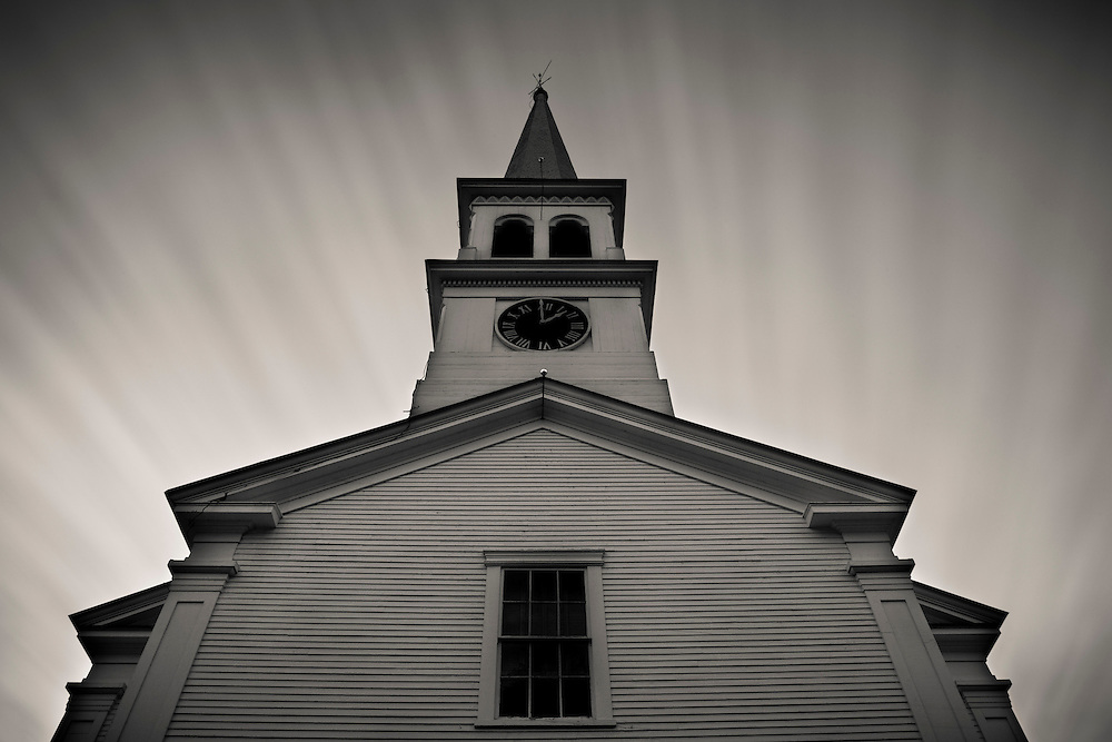 ominous sky and streaking clouds over a church steeple in Peacham, Vermont