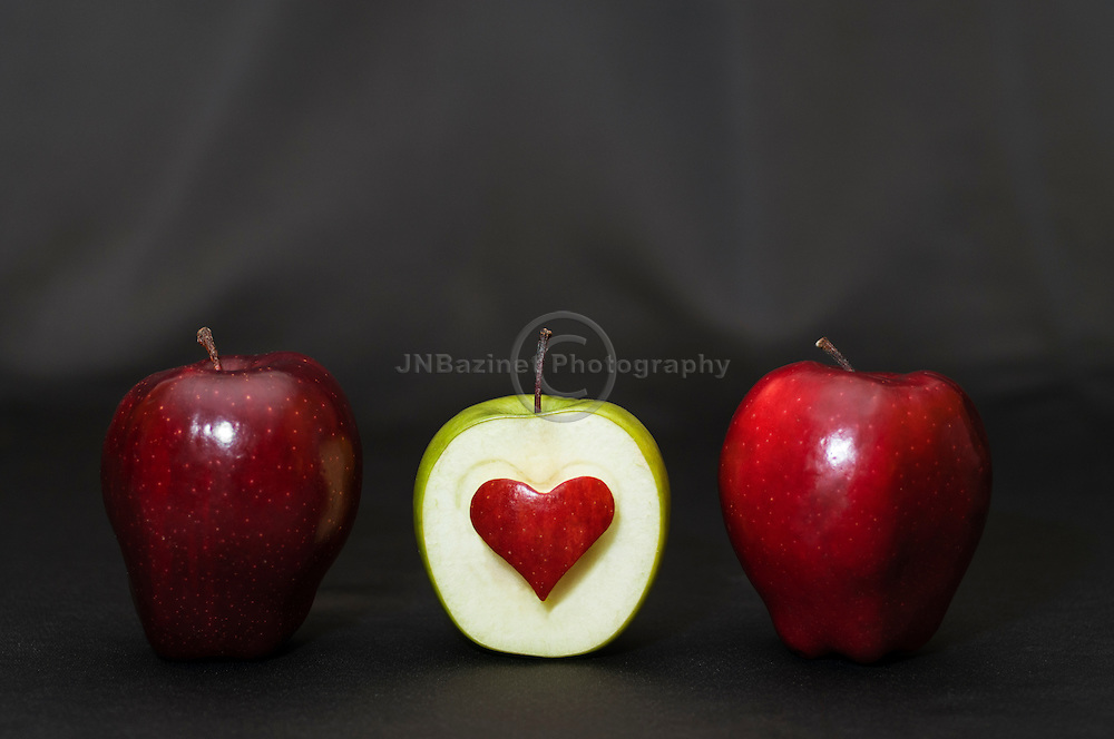 Two delicious red apples and granny smith apple with heart-shape cut-out.