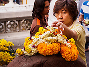 29 DECEMBER 2013 - BANGKOK, THAILAND:    A woman leaves flowers for the Patriarch at Wat Bowon Niwet in Bangkok. Somdet Phra Nyanasamvara, who headed Thailand's order of Buddhist monks for more than two decades and was known as the Supreme Patriarch, died Oct. 24 at a hospital in Bangkok. He was 100. He was ordained as a Buddhist monk in 1933 and rose through the monastic ranks to become the Supreme Patriarch in 1989. He was the spiritual advisor to Bhumibol Adulyadej, the King of Thailand when the King served as monk in 1956. There is a 100 day mourning period for the Patriarch. Although the Patriarch was a Theravada Buddhist, he was the Supreme Patriarch of all Buddhists in Thailand, including the Mahayana sect, which is based on Chinese Buddhism.      PHOTO BY JACK KURTZ