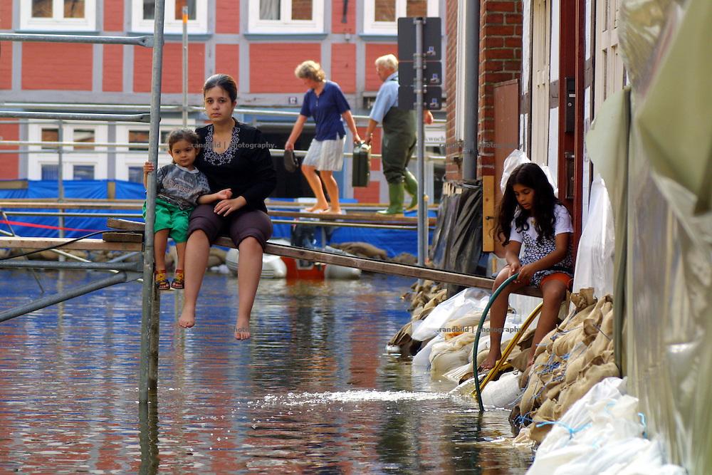 Elbe floods in Hitzacker, Germany. Kinder sitzen während des Jahrhunderthochwassers (August 2002) auf einem Gerüst in der von der Elbe überschwemmten Innenstadt Hitzacker in Lüchow-Dannenberg.