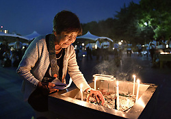 71. Jahrestag des Atombombenabwurfs in Hiroshima / 060816<br /> <br /> ***A woman remembers the victims of the U.S. atomic bombings of Hiroshima in front of the cenotaph at the Peace Memorial Park on Aug. 6, 2016, the 71st anniversary of the tragedy. In a Peace Declaration, Hiroshima Mayor called on world leaders to follow up U.S. President Barack Obama's historic visit to the western Japan city with trips of their own and to do more to abolish nuclear weapons***