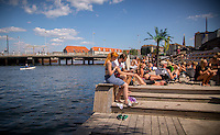 Copenhagen, Denmark- JULY 23, 2014: A couple relaxes at Kayak Bar, where a floating beach attracts tourists and locals alike on a sunny day. CREDIT: Chris Carmichael for The New York Times
