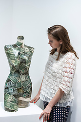 "© Licensed to London News Pictures. 08/06/2015. London, UK. A Sotheby's staff member looks at ""Venus aux dollars"" by Arman (est. £16,000 - £22,000), at the preview of ""To the Bearer on Demand"", a private collection of 21 works inspired by the US dollar, including Andy Warhol masterpieces, which will be auctioned on 1 and 2 July.  The collection is estimated to realise £50 million. Photo credit : Stephen Chung/LNP"