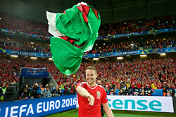 LILLE, FRANCE - Friday, July 1, 2016: Wales' Chris Gunter celebrates after a 3-1 victory over Belgium and reaching the Semi-Final with a red dragon Welsh flag during the UEFA Euro 2016 Championship Quarter-Final match at the Stade Pierre Mauroy. (Pic by David Rawcliffe/Propaganda)