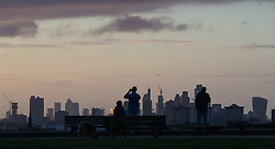 London, September 11 2017. Early morning walkers and runners pause on Primrose Hill to admire the London skyline as a new day breaks over the city. © Paul Davey