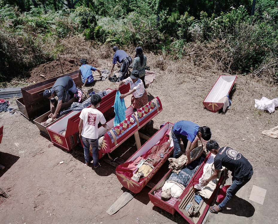 Family members put back the bodies of their dead relatives back in the coffin after cleaning and grooming.<br />