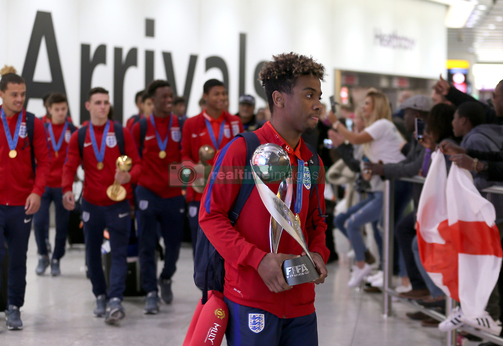 England's Angel Gomez walks back through the terminal with the trophy as the Under-17 World Cup winning side arrive back to the UK, at Heathrow Airport.