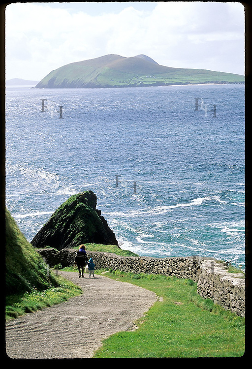 Mother and toddler walk down Dunquin Pier, traditional departure point for Great Blasket Island; Dingle Peninsula, Ireland.