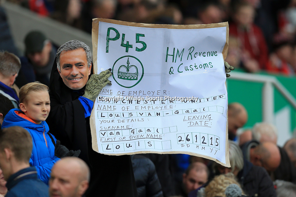 26th December 2015 - Barclays Premier League - Stoke City v Manchester United - A Stoke fan with a mask of Jose Mourinho's face holds up a banner depicting a P45 form with details of Man Utd manager Louis van Gaal - Photo: Simon Stacpoole / Offside.