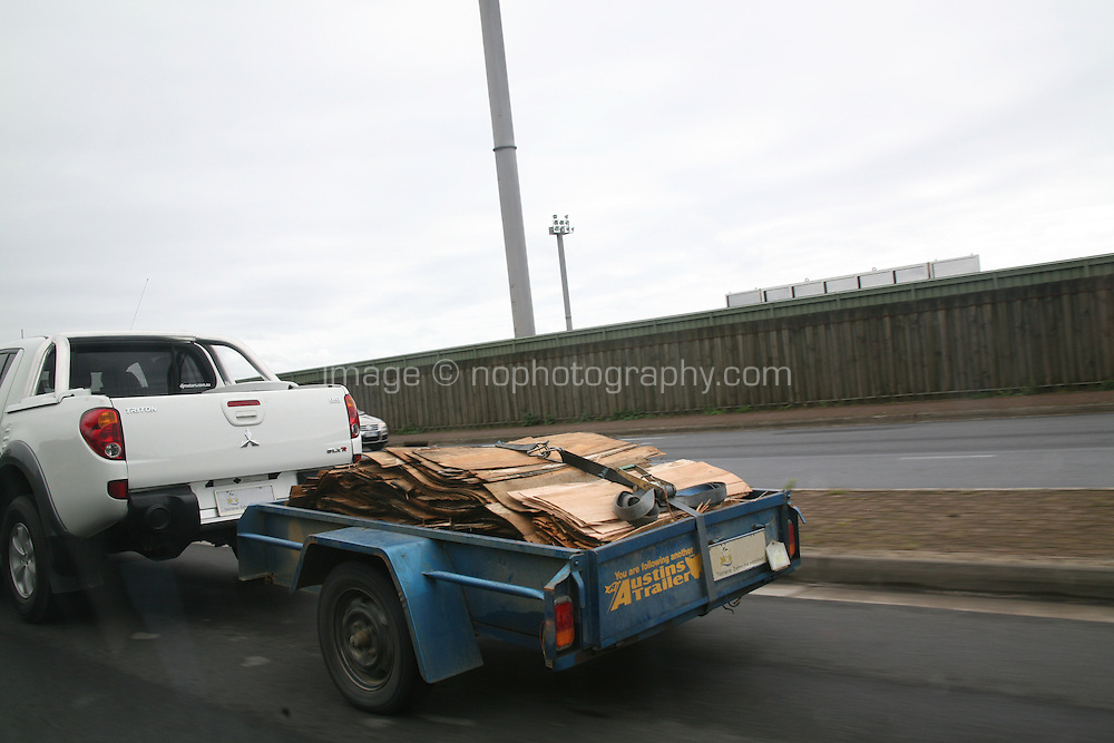 Pick up truck towing a trailer filled with wood on a road near Burnie Tasmania Australia