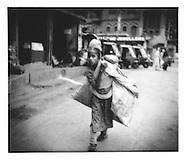 Kashmiri girl struggles under a heavy load in a Srinagar market, Indian Administered Kashmir.