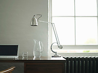 Desk with laptop lamp and jug of water