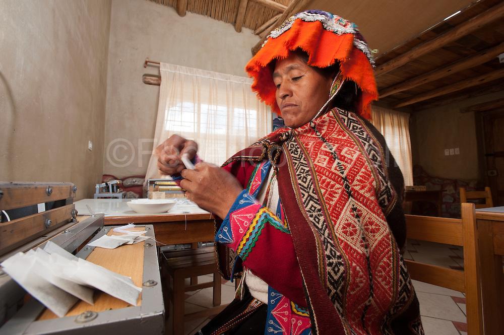 """Irma Pomacanchari live in a comunidad of  Potato Park, one of the side activities is the production of soaps and teas made with herbs of the area, she's preparing  manually some """"muña"""" bags."""