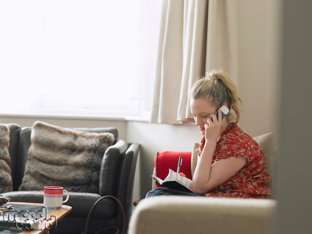 Woman using mobile phone sitting in living room elevated view