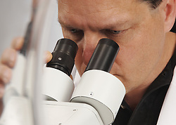 Closeup of a man looking into a microscope