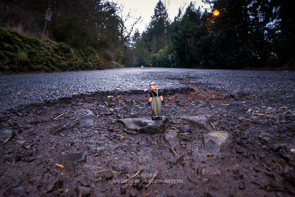 A mini-series following my 44mm-high Homies character Pelon, where he poses for photo ops at potholes on the streets of Mount Tabor Park.<br /> Leadership fixes potholes, not patching.<br /> Chronic neglect of Portland&rsquo;s streets is manifesting in the burgeoning number and size of dangerously large potholes across the city.  Here, pothole road damage is seen in Mount Tabor Park, Portland, Oregon. <br /> Engineering: From a technical perspective, a great deal of information can be gleaned from a deep pothole, as it provides a cross-section-view of the pavement structural section&hellip;or lack thereof, as in this case.  Here, the asphalt wearing surface is heavily pitted, highly oxidized and brittle, confirming many years of neglect.  The asphalt layer is minimal; confirming this road never received the maintenance originally planned. The large cobbles of the base course layer tell the story of a roadway constructed originally from poorly graded materials. Roadway base course should be well-graded, faceted aggregate so as to provide optimum particle interlock.  The conclusion is simple; this road has failed due to neglect and no amount of patching will restore a level of service &ndash; or service life &ndash; that should be reasonably expected of it.<br /> #portlandpotholes #PortlandOregon #MtTaborPark #potholes #neglect #deferredmaintenance #fail #safety #politics #civilengineering