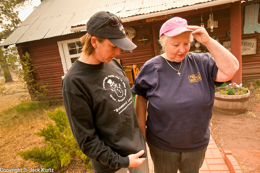 """05 JUNE 2011 - GREER, AZ:  Kristi Spillman (CQ LEFT) and Judy Cline (CQ) talk and say goodbye before leaving their businesses in Greer Sunday. Spillman operates the Frosty Bottom Cafe and Cline the """"Quacker Barrel"""" (CQ QUACKER) The fire grew to more than 180,000 acres by Sunday with zero containment. A """"Type I"""" incident command team has taken command of the fire.  PHOTO BY JACK KURTZ"""