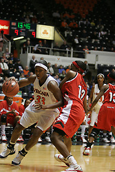 Tiffany Sardin (33) dribbles around a NC State defender in the first half.  Sardin had 16 points in the game.  The Wolfpack beat the Cavs 73-63.