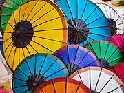 "11 MARCH 2016 - LUANG PRABANG, LAOS:  Colorful Lao parasols for sale in the handicraft market in Luang Prabang. Luang Prabang was named a UNESCO World Heritage Site in 1995. The move saved the city's colonial architecture but the explosion of mass tourism has taken a toll on the city's soul. According to one recent study, a small plot of land that sold for $8,000 three years ago now goes for $120,000. Many longtime residents are selling their homes and moving to small developments around the city. The old homes are then converted to guesthouses, restaurants and spas. The city is famous for the morning ""tak bat,"" or monks' morning alms rounds. Every morning hundreds of Buddhist monks come out before dawn and walk in a silent procession through the city accepting alms from residents. Now, most of the people presenting alms to the monks are tourists, since so many Lao people have moved outside of the city center. About 50,000 people are thought to live in the Luang Prabang area, the city received more than 530,000 tourists in 2014.      PHOTO BY JACK KURTZ"