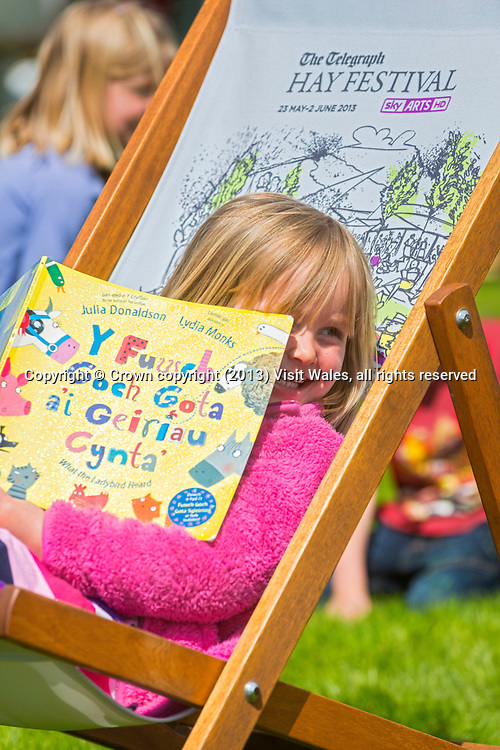 Girl sitting in deckchair reading book<br /> Hay Literary Festival 2013<br /> Hay-on-Wye<br /> Powys<br /> South<br /> Culture<br /> Arts<br /> Events