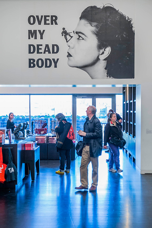 Over My Dead Body 1988 - Mona Hatoum a new Tate Modern exhibition. It presents around 100 works from the 1980s to the present day, including early performances and video, sculpture, installation, photography and works on paper. Mona Hatoum runs from 4 May to 21 August 2016.<br /> <br /> Highlights include:  Large-scale installations that fill entire rooms, including Impenetrable 2009, a suspended square formed of hundreds of delicate rods of barbed wire which hover above the floor, and Light Sentence 1992, in which walls of wire mesh lockers and a single lightbulb cast constantly moving shadows; Hot Spot 2013, a giant globe that uses red neon to outline the contours of the continents; a kinetic sculpture in which a rotating motor-driven arm draws circular lines across a large sandpit; and Homebound 2000, an installation of kitchen utensils and furniture which buzzes with electricity