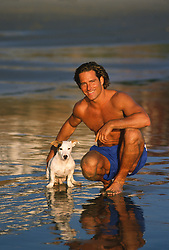 Man enjoying time on the beach with an adorable Jack Russell Dog