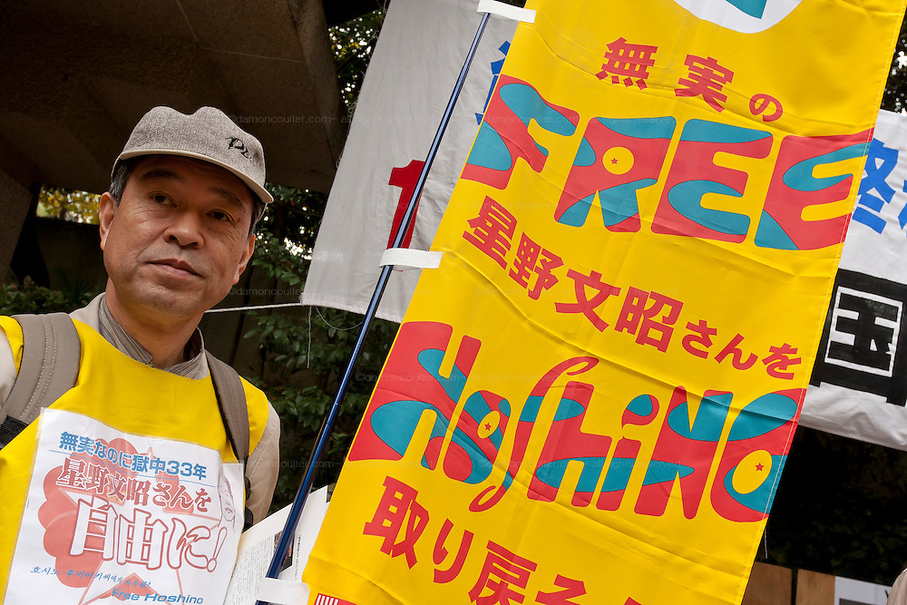 A Union activist holds a flag calling for the release of Fumiaki Hoshino, who was arrested in 1975 for the alleged killing of a policeman during riots in Okinawa in 1971 and sentenced to life imprisonment, at The National Worker`s Rally organised by Marxist groups and Doro Chiba labour union in Hibiya Park, Tokyo, Japan, Sunday, November 1st 2009