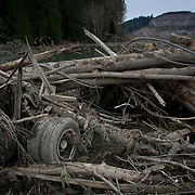 The rear wheels of a truck are shown in the mudslide debris near Oso, Wash. In the wake of Saturday's mudslide on Highway 530 in Snohomish County, there have been 176 reports of missing people or unaccounted individuals and the death toll has risen to 14. Photographed on Tuesday, March 25, 2014.