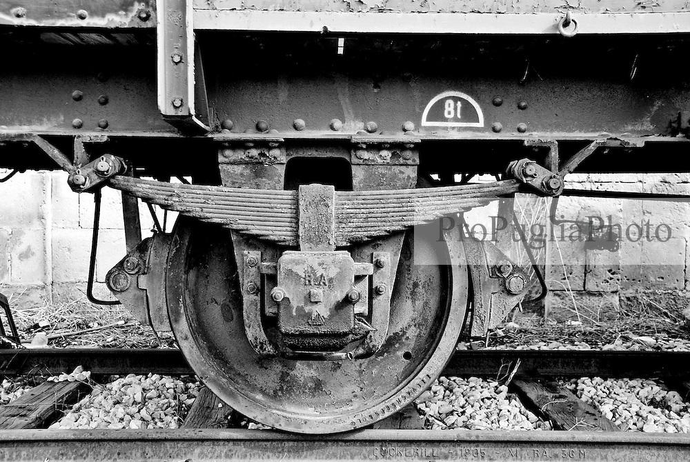 ruota di un vecchio vagone mercI parcheggiato su di un binario morto di una stazione delle ferrovie SUD EST.  Reportage che racconta le situazioni che si incontrano durante un viaggio lungo le linee ferroviarie SUD EST nel salento.