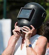 Middletown, New York - A woman uses a welding helmet to watch a partial solar eclipse on Alumni Green at SUNY Orange on Aug. 21, 2017.