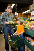 Mature man looking at produce with grandson in farmer's market