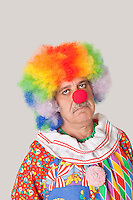 Portrait of sad senior male clown against colored background