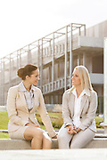 Young businesswomen looking at each other while sitting against office building